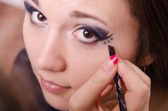 De make-upkunstenaar schildert een punt over pijlen in de ogen van het meisje Royalty-vrije Stock Afbeeldingen