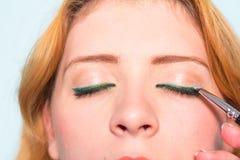 De make-upkunstenaar schildert ogen van vrouw makeup stock afbeelding