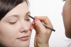 De make-upkunstenaar tijdens make-up brengt wenkbrauwpotloodmodel Royalty-vrije Stock Fotografie