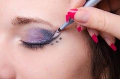 De make-upkunstenaar trekt pijlen op witte meisjesleeftijden Royalty-vrije Stock Afbeelding