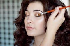 De make-upvrouw die van het oog oogschaduwpoeder toepast Maak omhoog kunstenaar die beroeps doen omhoog van jonge vrouw maken Stock Fotografie
