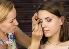 De make-upvrouw die van het oog oogschaduwpoeder toepast De stilist doet goedmaakt wijfje door eyeliner stock foto