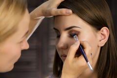 De make-upvrouw die van het oog oogschaduwpoeder toepast De stilist doet goedmaakt wijfje door eyeliner royalty-vrije stock afbeeldingen