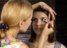 De make-upvrouw die van het oog oogschaduwpoeder toepast De stilist doet goedmaakt wijfje door eyeliner stock afbeelding