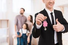 De makelaar in onroerend goed in kostuum houdt sleutels met sleutel FOB- in vorm van huis De jonge familie kijkt flat royalty-vrije stock foto's