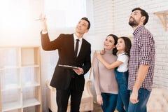 De makelaar in onroerend goed in kostuum toont familiehuis dat zij hebben gekocht Concept het kopen van huis Onroerende goederen  stock foto's