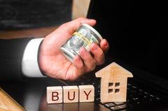 De makelaar in onroerend goed` s hand houdt een bundel van geld achter het miniatuurhuis Het concept het kopen en onroerende goed stock afbeeldingen