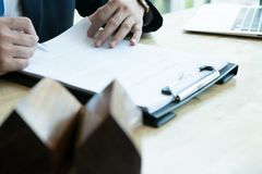 De makelaar in onroerend goed verklaart de overeenkomst van de hypotheeklening aan zijn cliënt Echte est stock afbeelding