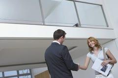 De makelaar in onroerend goed And Woman Shaking dient Nieuw Huis in stock fotografie