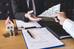 De makelaar van de landgoedagent ontvangt geld van cliënt na het ondertekenen van onroerende goederen overeenkomstencontract met  stock afbeelding