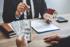 De makelaar van de landgoedagent ontvangt geld van cli?nt na het ondertekenen van onroerende goederen overeenkomstencontract met  royalty-vrije stock foto's