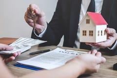 De makelaar van de landgoedagent ontvangt geld van cli?nt na het ondertekenen van onroerende goederen overeenkomstencontract met  stock afbeelding