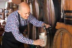 De maker die van de bejaardewijn wijn van hout nemen stock afbeeldingen