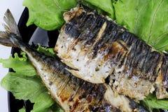 De makreel wordt geroosterd op een elektrische grill Geroosterde vissen met citroen en salade stock foto