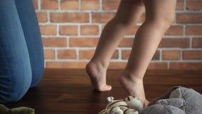 De mama onderwijst haar babymeisje om te lopen Van de sparrenstappen van het babymeisje langzame de motie hd video stock footage