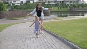 De mammaspelen halen een klein meisje in stock footage