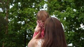 De mammaspelen met weinig dochter, werpt op baby met zijn handen, is het kind gelukkig en lacht meisjespelen in de handen stock videobeelden