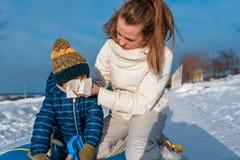 De mammavrouw veegt haar jongen van de kinds neus 3 jaar oud, buiten in de winter af, hoestsnot, koude en griep, op een koude de  stock fotografie