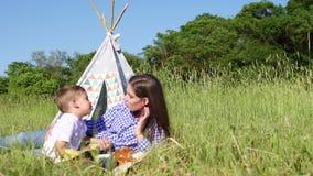 De mammazoon eet bij een picknick in het bos stock video