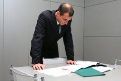 De man achter een lijst met documenten Stock Foto