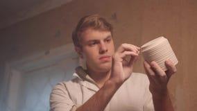De man achter de spinnende pot van het Pottenbakkers` s wiel keramiek aardewerk, het macro schieten stock video