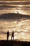 De man & de vrouw koppelen op strand bij zonreeks Royalty-vrije Stock Fotografie