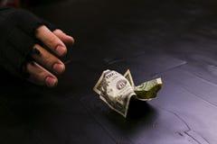 De man bereikt voor een dollarrekening Dag voor de uitroeiing van armoede stock foto