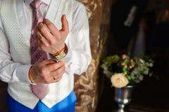 De man bevestigt de manchetten op het witte overhemd en modieuze vest en blauwe broek met dure gouden toebehoren, horloges, ringe stock foto's