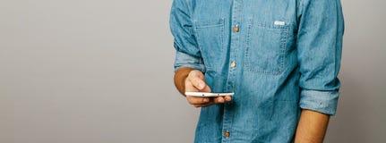 De man is bezig op de telefoon Schuifwebsite Denim blauw overhemd royalty-vrije stock afbeeldingen