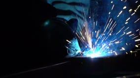 De man bij de bouw last metaaldetails Donkere ruimte Blauw licht en rook van lassen Vonken tegen een donkere achtergrond stock video