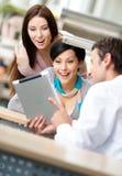 De man bij de lezingszaal toont tablet aan twee vrouwen Stock Fotografie