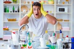 De man bij het moeten wordt gefrustreerd schotels wassen die royalty-vrije stock afbeelding
