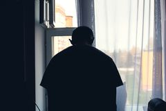 De man bij het venster, die zijn hoofd neer in depressie buigen, wil zelfmoord begaan stock afbeeldingen