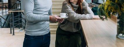 de man bracht koffie, thee aan het meisje dat bij de lijst zit wil op de hoogte brengen worden royalty-vrije stock afbeeldingen