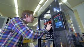 De man controleert de 3d printer en plaatst sommige opties op het scherm 4K stock footage