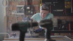 De man die in beschermingsglazen een houten raad met een kleine cirkelzaag op de lijst in de workshop snijden meubilair stock videobeelden