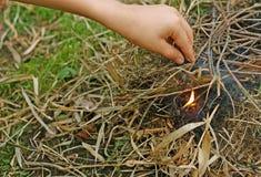 De man die brand aan het droge gras plaatst Royalty-vrije Stock Fotografie