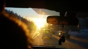 De man die de auto drijven onder de bezinning van de zonsonderganghemel in de achteruitkijkspiegel stock video
