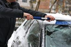 De man die de auto van sneeuw schoonmaakt Royalty-vrije Stock Foto