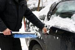De man die de auto van sneeuw schoonmaakt Stock Foto