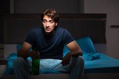 De man die in het bed onder spanning drinken stock afbeeldingen
