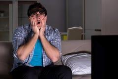 De man die op 3d televisie letten laat bij nacht Stock Foto's