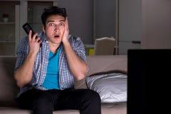 De man die op 3d televisie letten laat bij nacht Royalty-vrije Stock Afbeelding