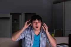 De man die op 3d televisie letten laat bij nacht Stock Afbeelding