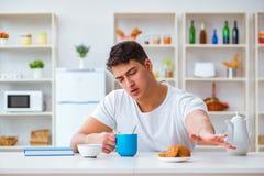De man die in slaap tijdens zijn ontbijt na overwerk vallen Stock Foto
