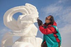 De man doet een beeldhouwwerk van sneeuw Royalty-vrije Stock Foto