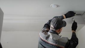 De man doet reparaties in de flat, schildert de persoon met leeswijzerpleister het vormen op het plafond stock footage