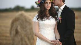 De man draagt een kroon van bloemen op het hoofd van het meisje Middelgroot schot stock video