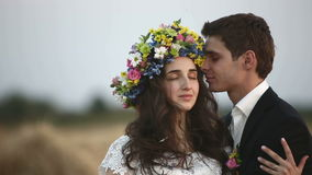 De man draagt een kroon van bloemen op het hoofd van het meisje Middelgroot schot stock videobeelden