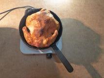 De man draait een gebraden kip in een pan op een hotplate Kokende gebraden kip stock foto's